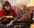 Woman reading to a woman in a wheelchair